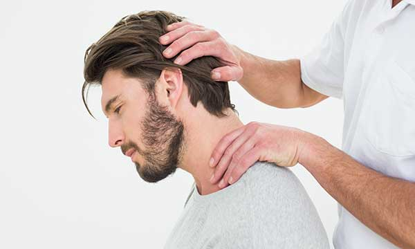male patient getting his neck examined by doctor
