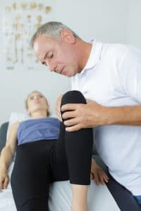 Chiropractor examining female patients knee
