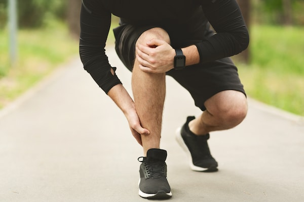 male runner holding his knee and ankle due too joint pain
