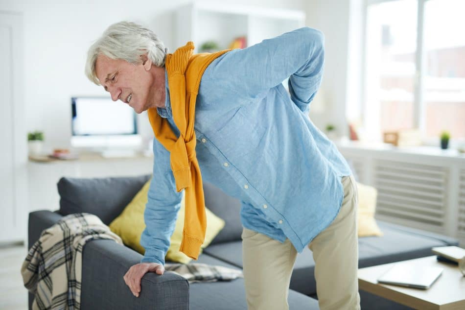 elderly man having back pain from sitting in his chair