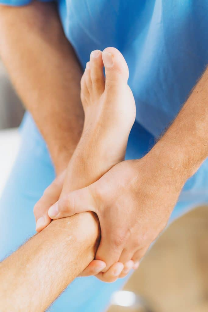 chiropractor adjusting patients ankle and foot