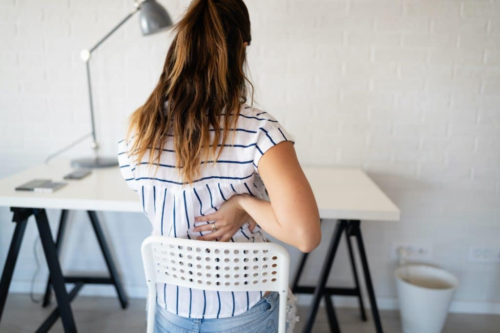 young lady having upper back pain due to sitting in her chair