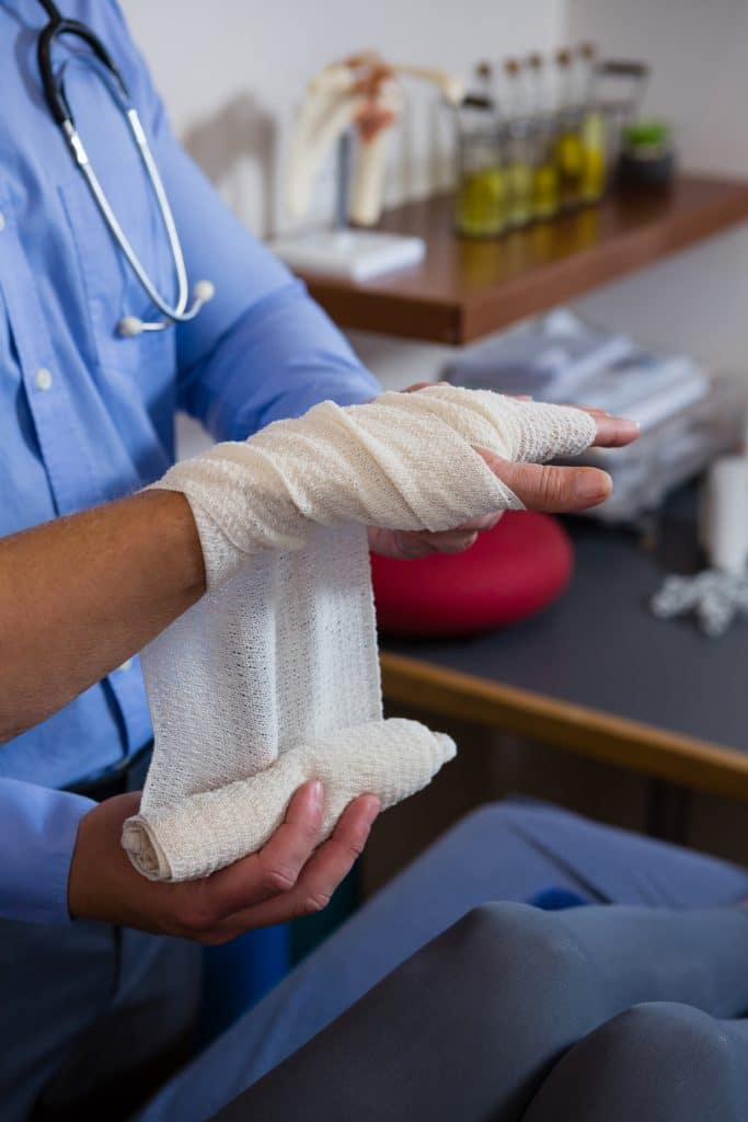 doctor wrapping a patients wrist with a bandage