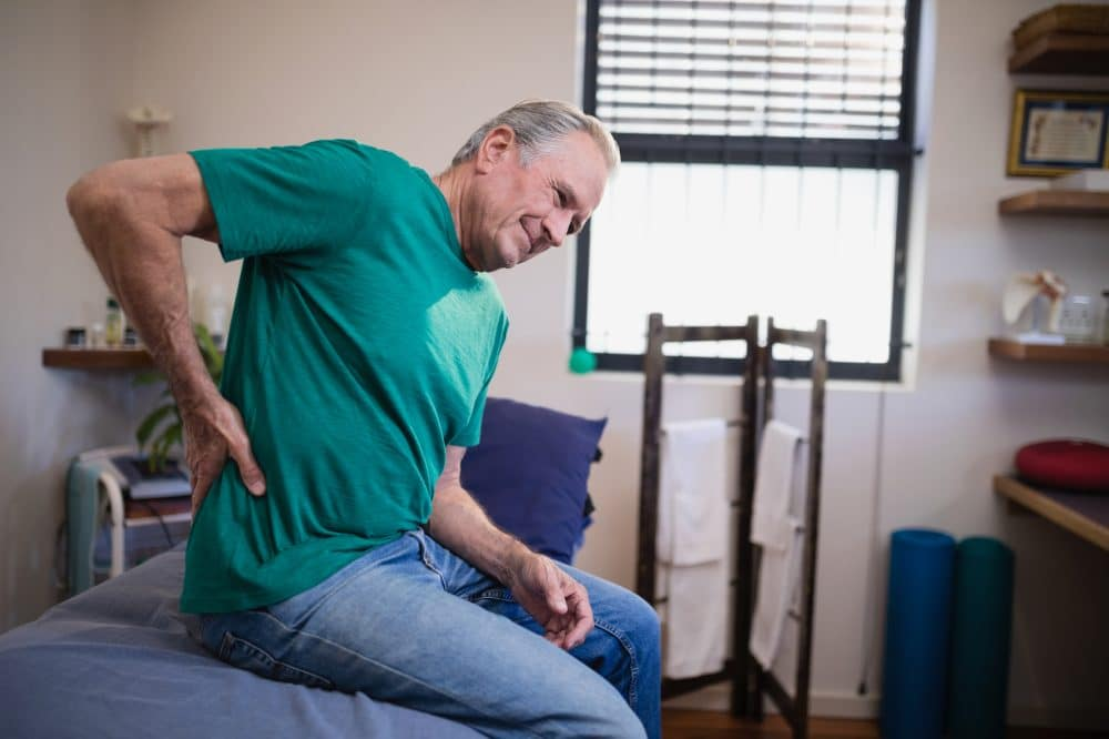 elderly man holding his back due to pain