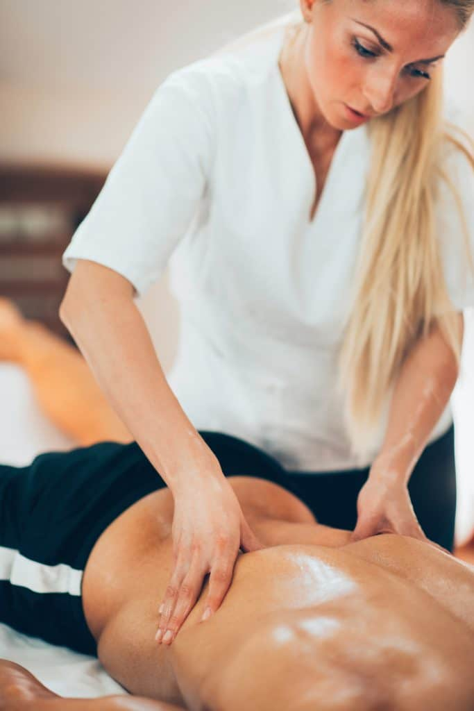 massage therapist massaging patient lower back