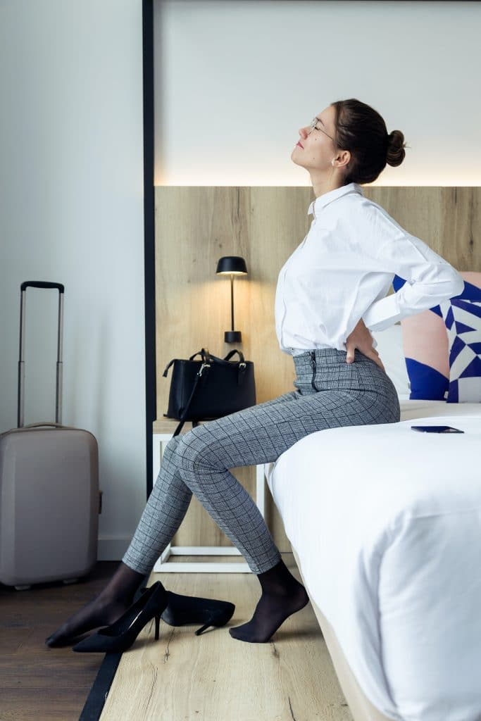 young woman sitting on her bed having back pain