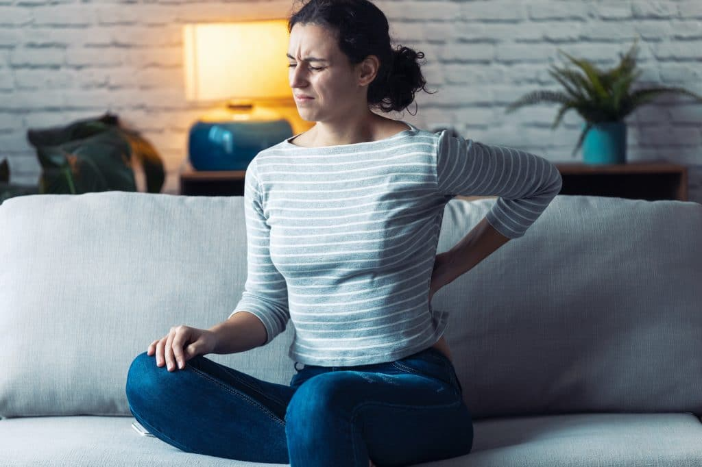 young woman sitting on the couch having back pain
