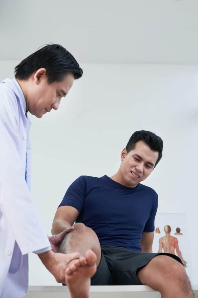 chiropractor examining patient knee
