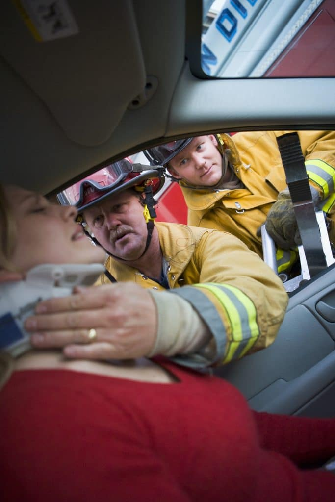 firefighters helping a woman out of a car that was in an accident