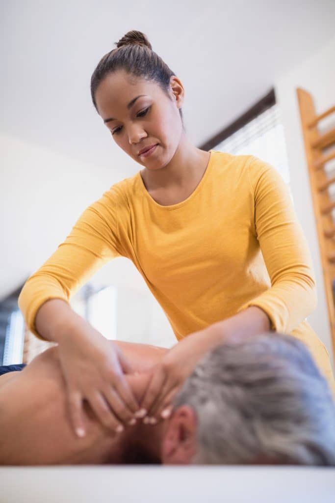 massage therapist massaging patients neck