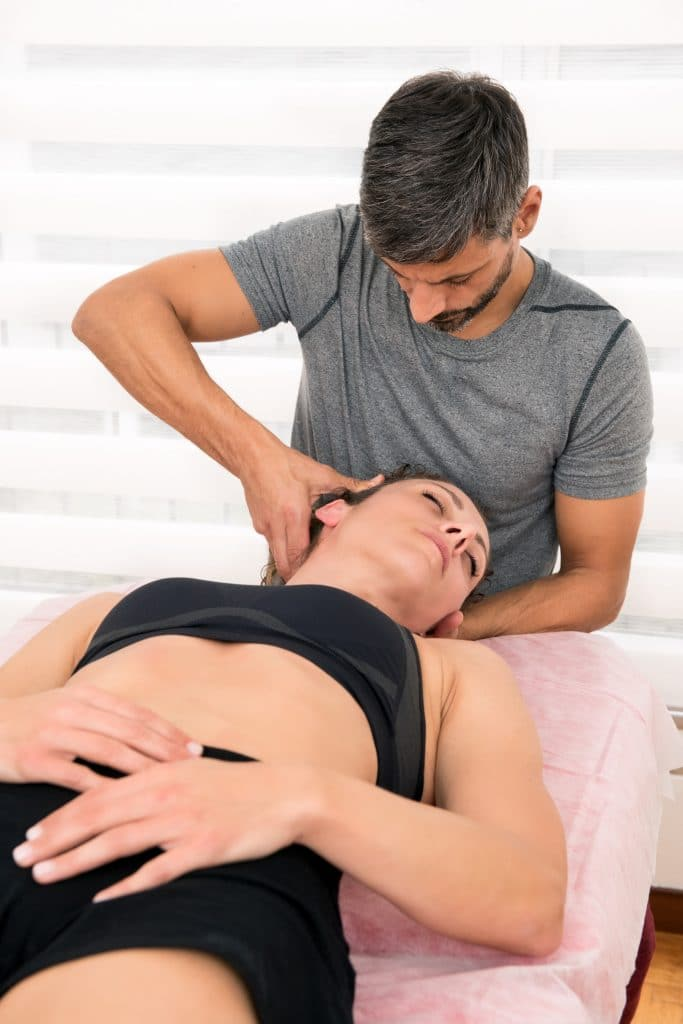chiropractor adjusting female patients neck