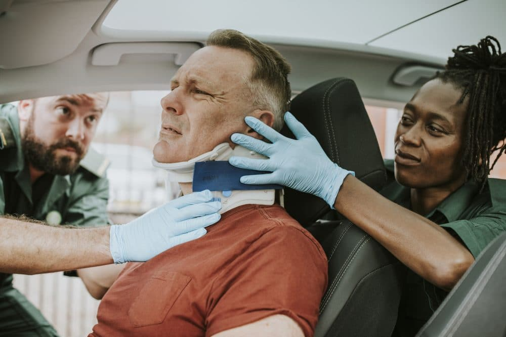 paramedics helping a man out of a recent car accident