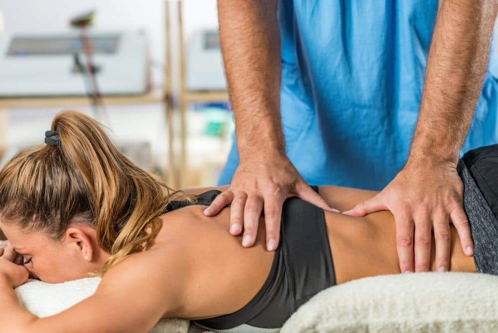 chiropractor adjusting female patients back