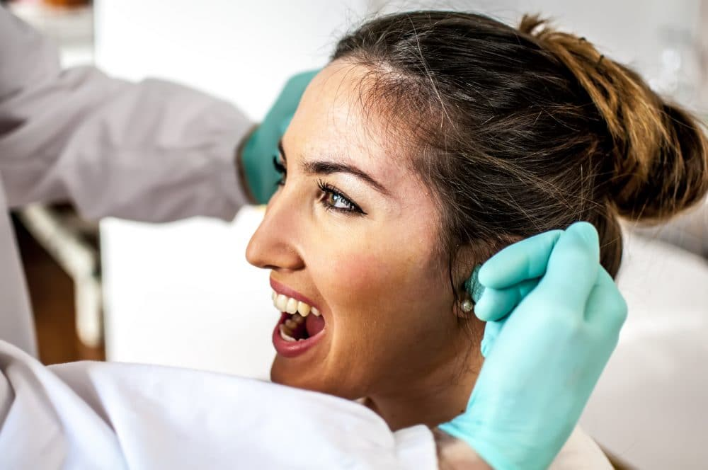 young lady getting examined by her doctor for tmj pain