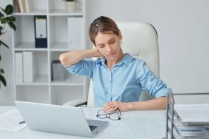 young woman having neck pain from looking at her laptop
