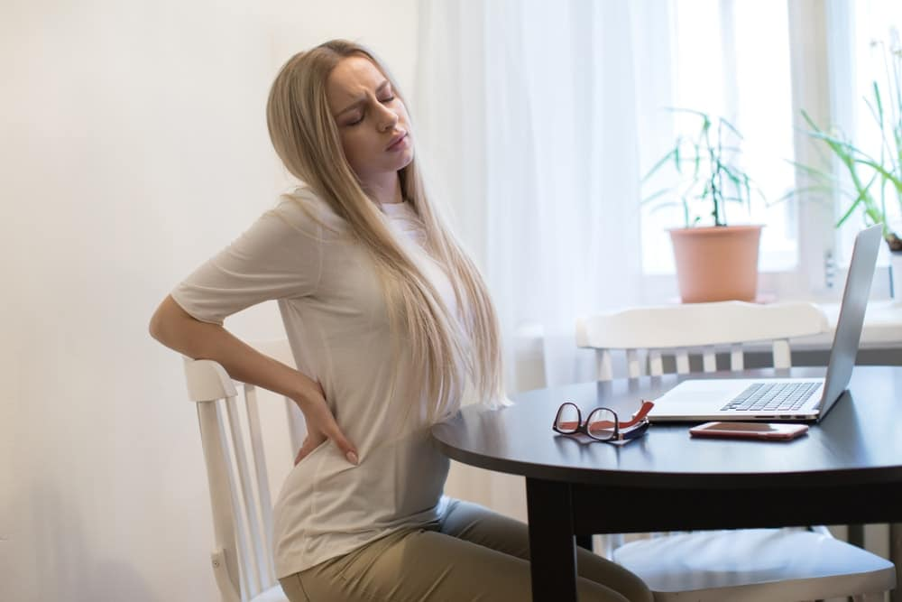 young woman sitting on the chair having back pain