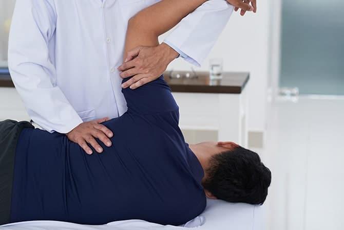 Chiropractor examining a patient with frozen shoulder