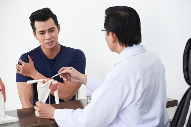 Male patient having a doctor's consultation for arm pain