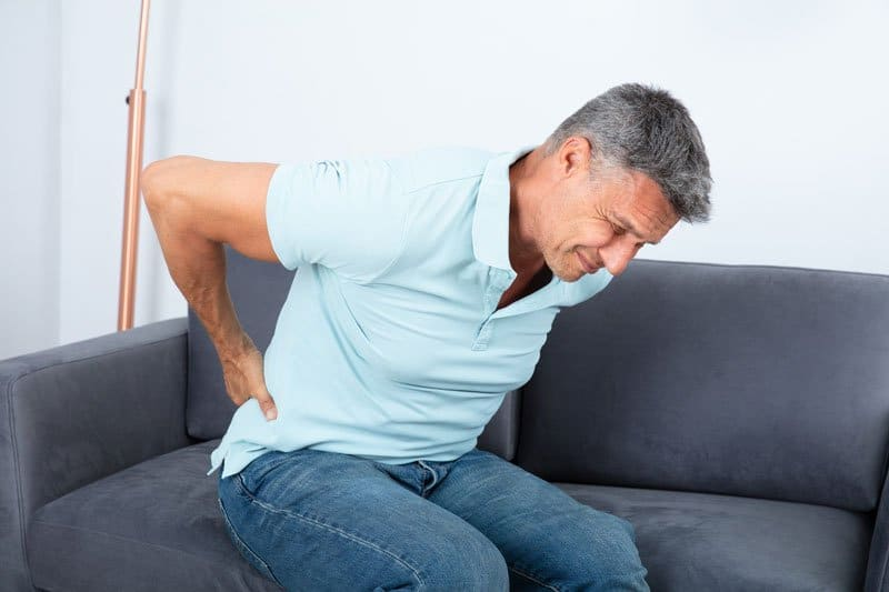 Man on a couch massaging his back due to radicular pain.